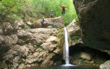 Un aventurier qui saute une petite cascade pour atterrir dans une vasque
